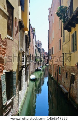 A narrow canal flowing through a neighborhood in Venice, Italy. Houses are submerged in water and laundry hangs on lines from windows. Boats are on the water over reflections of sky and buildings #1456549583