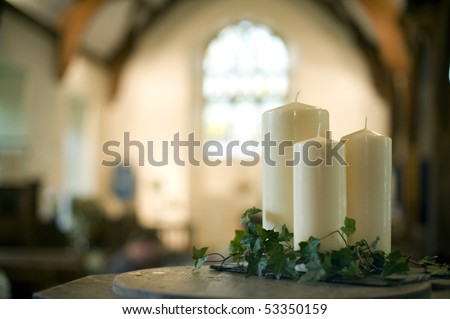 a narrow depth of field image of the interior of a church focusing only on three white candles