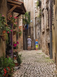 A narrow stone paved street with ancient houses built of stones and many bloom flowers in pots. Traditional landscape of old italian city. Father and son walking in small medieval town Sermoneta.