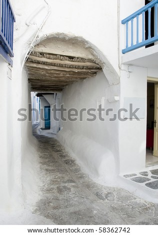 A narrow street in the Greek island going under the arch - is typical for Greece and the Greek Islands