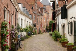 A narrow street with flower pots in the old medieval center of the Dutch medium-sized historic city of Amersfoort.