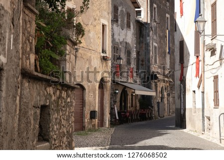 A narrow  traditional street paved with stone among stone houses in a medieval small town Sermoneta not far from Rome. Traditional Italian restaurant under the shed is located in one of the buildings.