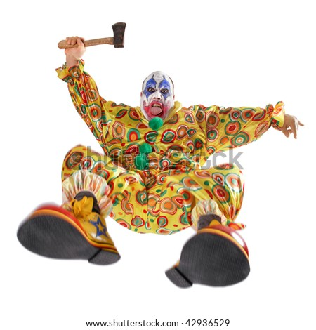 A nasty evil clown, angry, jumping, and about to hack you to bits.  Motion blur on the knees and shoes. - stock photo