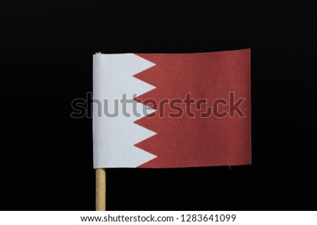 A national flag of Bahrain on toothpick on black background. A white field on the hoist side separated from a larger red field on the fly by five white triangles in the form of a zigzag pattern. #1283641099