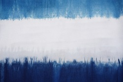 A natural indigo dye on cotton fabric showing color flow and its pattern.  Horizontal blue and white. At center is good for texts, copy space and advertisement. Material, object, background, design.
