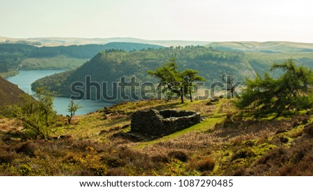 A natural landscape in the hills, an abandoned slate house on top of the mountain overlooking the water reservoir in the valley.  #1087290485