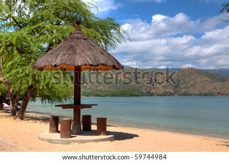 A natural leaf covered beach hut with wood stools in timor leste, in HDR