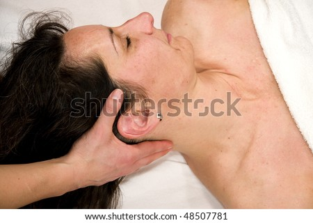 stock photo : a natural mature woman having a massage at her neck muscles