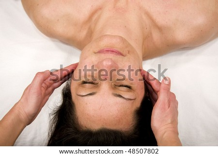 stock photo : a natural mature woman having a massage at jaw and at her ...