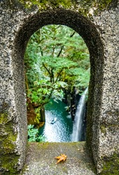 A nature landscape view through stone wall arch of fresh rain forest waterfall of Takachino George, Miyazaki, Kyushu, Japan