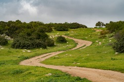 A nature path going through fields and hills in the Adullam region of Israel, on an overcast day.