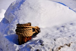 A nautical rope type fence covered with deep snow with the timber post wrapped with heavy rope as the focal point of the winter season image on a frigid cold day.