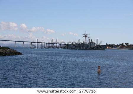 A Navy Battle ship in San Diego Harbour.  Coronado Bridge in the background.
