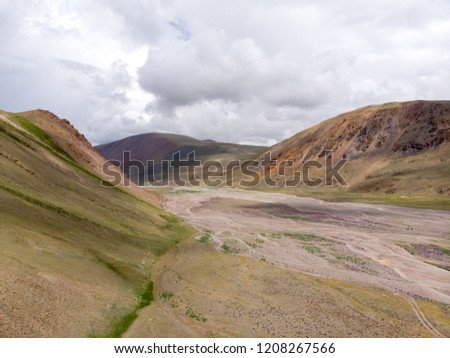 a nearly dried torrent bed with slopes in background