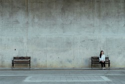 A nearly symetry picture of two bench at the loft-style wall, one of them is empty and another is sit by the woman.