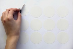 a neat female hand peels off the round white sticker of the plotter trimming.  mockup stickers