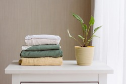 a neat stack of folded women's clothing in natural colors on a white wooden chest of drawers, a green houseplant near the window with white tulle