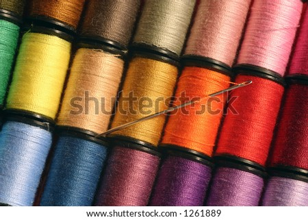 A needle at rest among colorful sewing threads.