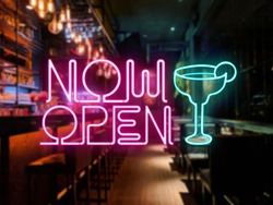 A neon Now Open sign in front of a bar or pub. Slightly blurred bar or tavern background. Nightlife concept. Pink and teal colors.