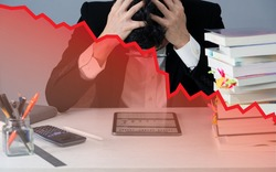a nervous business man in desk when business crash with red stock price chart plummet, slow growth economy