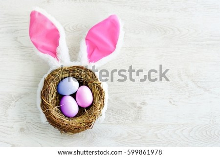 A nest with three colored Easter eggs and bunny ears at home on Easter day. Celebrating Easter at spring. Painting eggs.