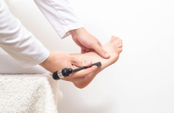 A neurologist doctor checks the cheddock reflex in a patient with a neurological moth. Pathological sole reflex on the side of the foot, copy space, neuropathology