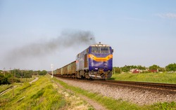 A new American-made diesel locomotive carries a heavy train of wagons to a freight station in the Ukrainian