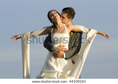 A new bride with arms outstretched is held and kissed by her handsome groom.  Blue sky background