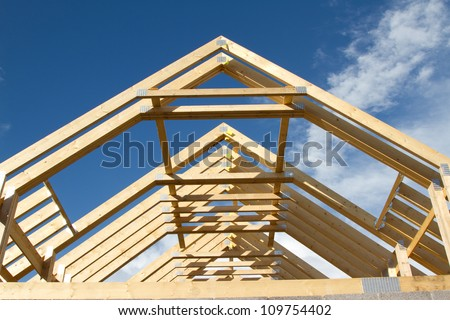 A new build roof with a wooden truss framework making an apex against a blue sky with cloud - Build wood roof abcs roof framing ...