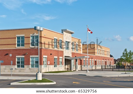 A new Canadian elementary school building with flagpole and parking lot.