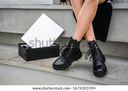 a new collection of women's shoes autumn winter '20 / 21. The girl bought new shoes. Legs in black boots. Boots in a box Stock foto ©