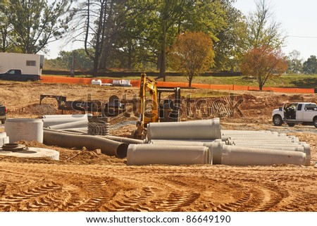 A new construction site with heavy equipment and concrete conduit