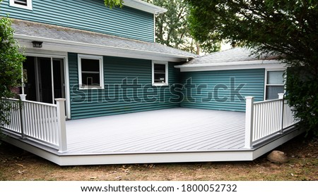 A new deck is installed on the back of a house with composite material and white hand rails. Stock photo ©