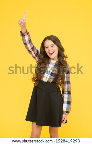 A new genius. Happy schoolgirl got genius idea. Genius little child pointing finger up. Wonder kid on yellow background. Genius in education. Future bright when school insight.