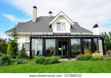 A new house with a garden in a rural area under beautiful sky - stock photo