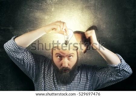 A new idea concept. Image bearded man twists a light bulb in his head as a metaphor of a new idea. Eureka!