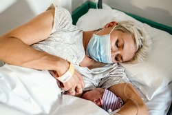 A new mother nursing her newborn little boy in facial mask during pandemic