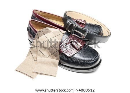 A new pair of slip on dress shoes with tan socks and a black leather belt