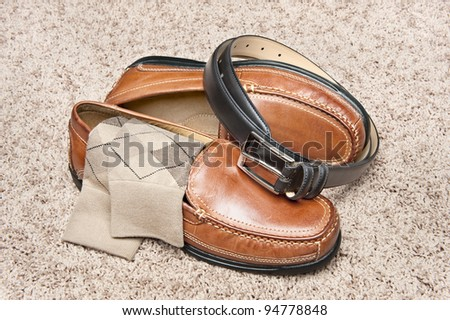 A new pair of tan leather shoes with socks and belt on beige carpet
