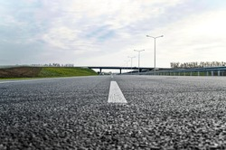 A new road with a dividing strip and lighting poles. Road construction.