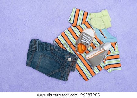 A new set of baby clothing on a purple blanket