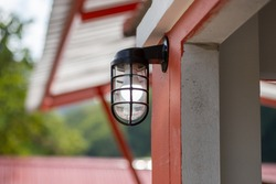 A new small lamp Installed on the wall in front of the house, in front of the building with white energy-saving lamps