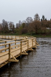 A new wooden boardwalk above the pond water, dark waves, cloudy skies, dry grass, trees without leaves in the early spring day in Durbe, Latvia. Nature trail with bench and lanterns.