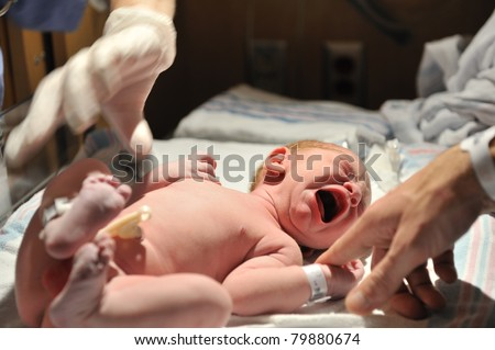 A newborn baby cries moments after birth while dad reaches out to comfort. Has Model Release.
