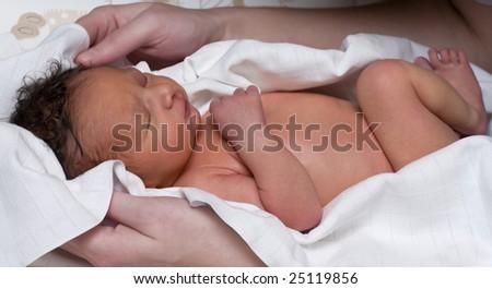 A newborn baby in a cloth after bath