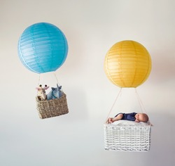 A newborn baby in the basket of an air balloon with his stuffed animal friends