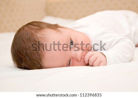 A newborn baby is thinking and finger sucking
