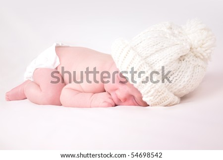 A newborn baby is wearing a white hat and laying down sleeping on a soft white background. Use the photo to represent life, parenting or childhood.