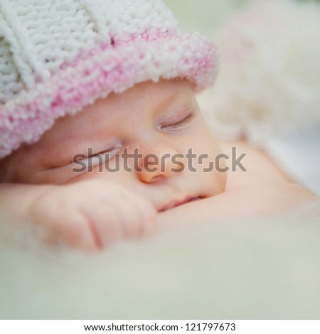 A newborn baby is wearing a white hat and sleeping on a soft white background. Childhood or parenting concept.