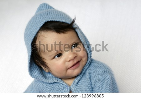 A newborn baby is wearing blue cardigan with hood smiles on a soft white background. Concept photo to to represent life, parenting or childhood.